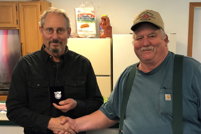 Greg Miner receives his 100,000 PITA milestone pin from Jim Bradbury